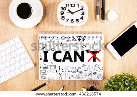 I can, self motivation concept. Crossed out letter 'T so that it reads i can on notepad with business charts placed on office desktop with smartphone and other items. Mock up - stock photo