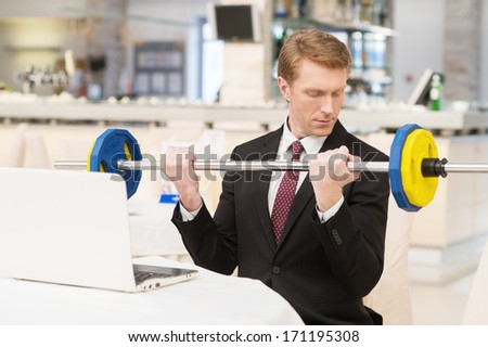 I choose healthy lifestyle. Confident young red hair man in formalwear sitting at the restaurant and holding a dumbbell - stock photo