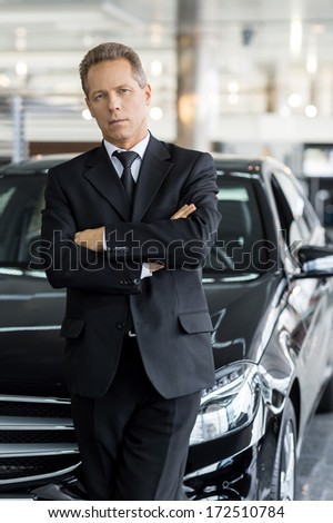 I choose only the best. Confident grey hair man in formalwear standing in front of car and looking at camera
