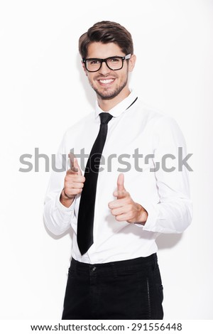 I choose you! Cheerful young man pointing at camera and smiling while standing against white background - stock photo