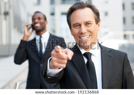 I choose you! Confident senior man in formal wear pointing you and smiling while African man talking on the mobile phone in the background   - stock photo