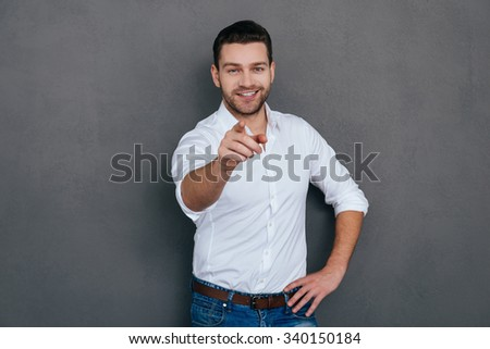 I choose you! Handsome young man pointing you and smiling while standing against grey background  - stock photo