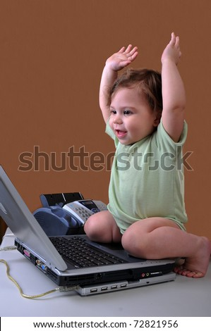 I did it! Baby sitting at her laptop, raising her arms as it to be finishing a project she had worked hard on. - stock photo