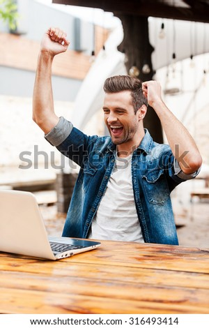 I did it! Cheerful young man keeping arms raised and expressing positivity while sitting at the wooden table outdoors - stock photo