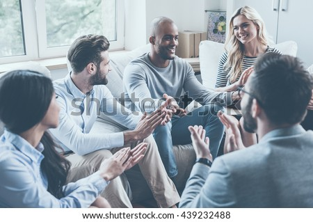 I did it! Group of young cheerful people sitting in circle and applauding while one man gesturing and smiling - stock photo