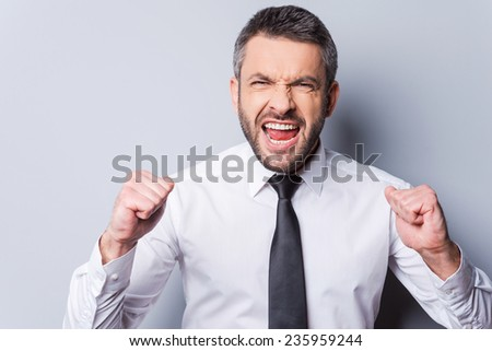 I did it! Happy mature man in shirt and tie gesturing and shouting while standing against grey background - stock photo
