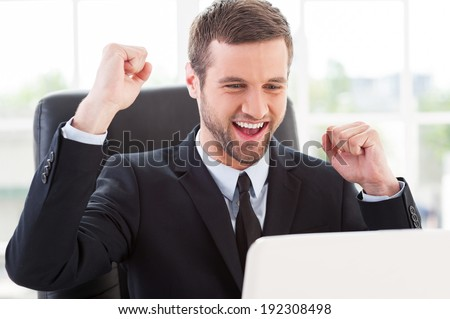 I did it! Happy young man in formal wear looking at computer monitor and gesturing while sitting at his working place - stock photo