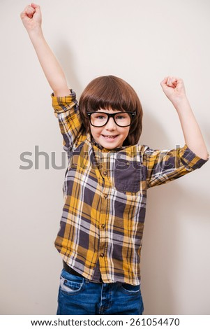 I did it! Little boy in eyewear keeping arms raised and smiling while standing against grey background - stock photo