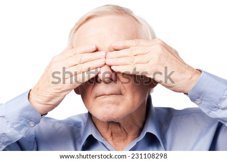 I did not see anything. Frustrated senior man covering his eyes by hands while standing against white background   - stock photo