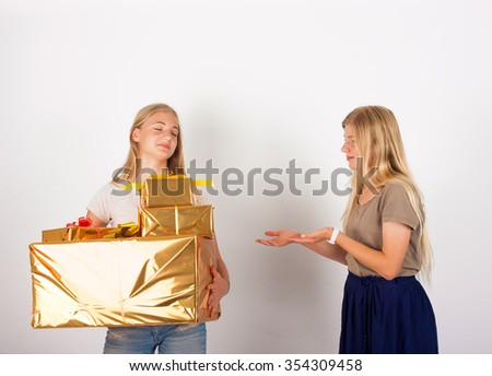 I don't give from my presents to you - Selfish girl does not want to share her gift boxes with her sister.