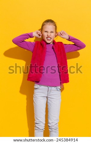 I don't want to hear it. Young blond girl stops her ears. Three quarter length studio shot on yellow background.