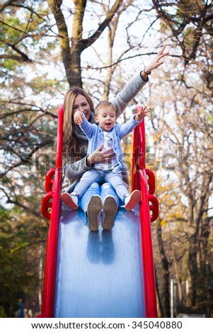 I feel like on top of the world, mother and her little son on slide in playgraund having fun, autumn day - stock photo