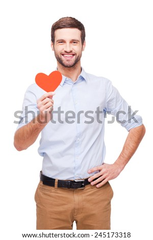 I give you my heart! Handsome young man holding heart shaped valentine card and smiling while standing isolated on white background   - stock photo