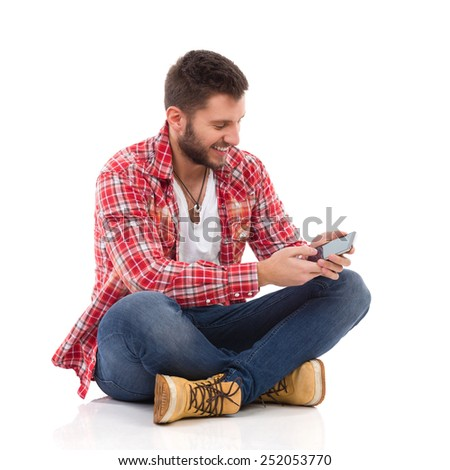I got my message. Handsome young man in jeans and lumberjack shirt sitting on floor with legs crossed and using a smart phone. Full length studio shot isolated on white. - stock photo