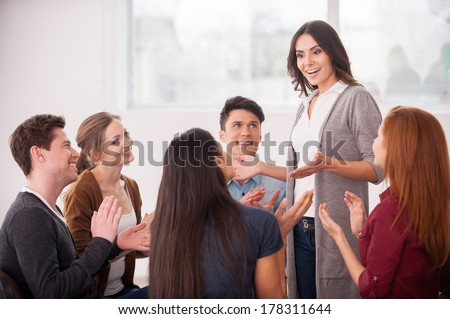 I have an issue. Group of people sitting close to each other while man telling something and gesturing - stock photo