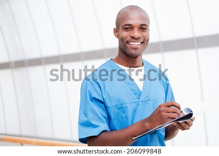 I have good news for you. Cheerful young African doctor in blue uniform writing something in clipboard and smiling while touching his chin with pen - stock photo