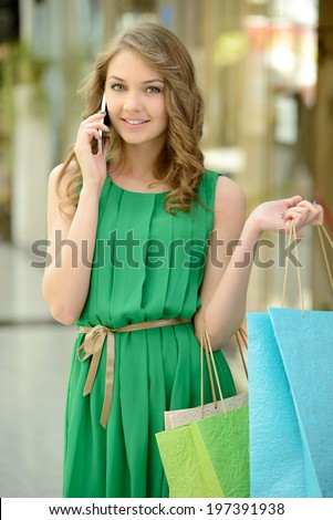 I have got a lot on sale. Beautiful young woman in blue dress holding shopping bags and talking on the mobile phone - stock photo