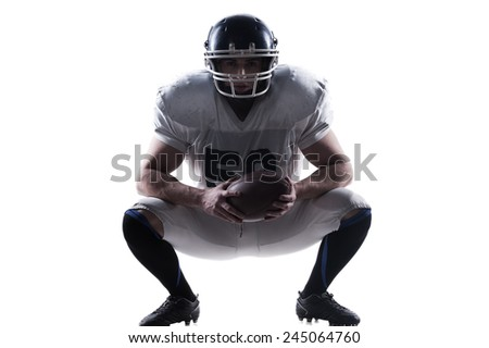 I have no equal in this sport.  American football player holding ball and wearing helmet while sitting against white background  - stock photo