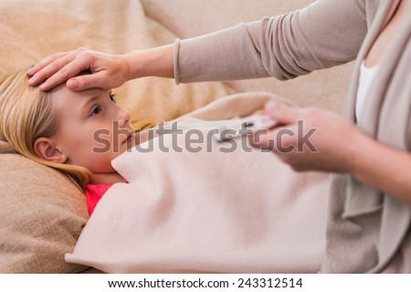 I hope it is not flu. Mother holding thermometer and touching forehead of her ill daughter lying on the couch  - stock photo