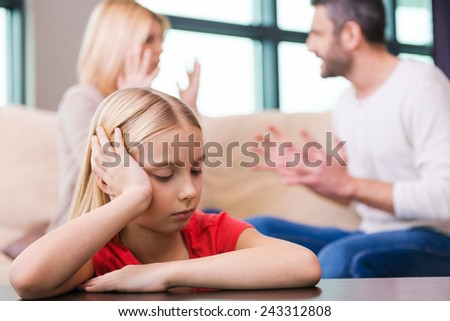 I hope they will work it out. Sad little girl leaning at the table and holding head in hand while her parents shouting at each other in the background - stock photo