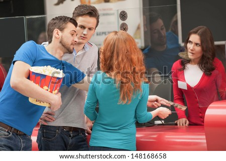 I�¯�¿�½ in hurry! Young rude men trying to buy a movie ticket without standing in line