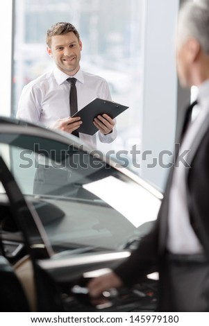 I knew you like this car. Handsome young classic car salesman standing in the dealership and helping a client to make a decision - stock photo
