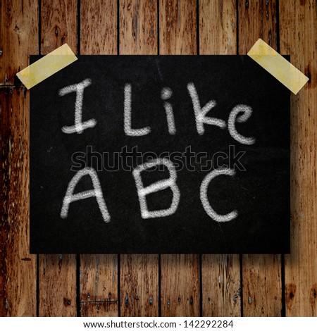 I like ABC on message note with wooden background - stock photo