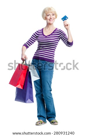 I like shopping! Happy middle aged woman showing her credit card and holding shopping bags while standing isolated on white background - stock photo