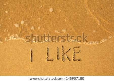 I Like - text written by hand in sand on a beach, with a soft wave.