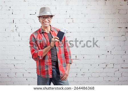 I like traveling! Handsome arabic hipster man in hat holding passports and boarding tickets while standing against brick wall. - stock photo