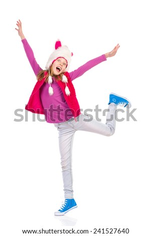 I like winter. Girl in funny fur hat is standing on one leg and shouting with arms outstretched. Full length length studio shot isolated on white. - stock photo