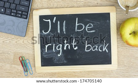 I'll be right back written on a chalkboard at the office - stock photo