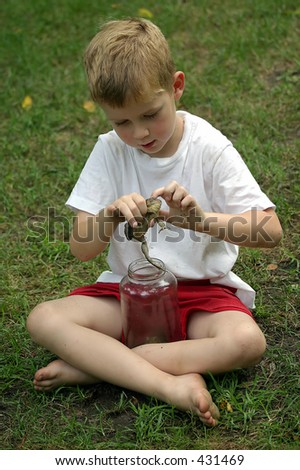 I'll hug him and squeeze him.... A little boy petting a toad. - stock photo