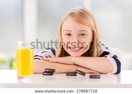 I love cookies! Cheerful little girl leaning at the table with cookies and glass of juice on it  - stock photo