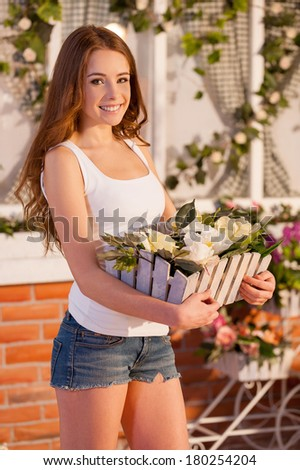 I love flowers! Attractive young woman holding a potted plant and smiling at camera while standing outdoors - stock photo