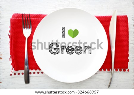 I love Green concept on white plate with fork and knife on red napkins