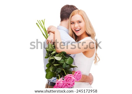 I love him so much! Beautiful young loving couple hugging while woman holding bouquet of pink roses and smiling and both standing isolated on white background   - stock photo