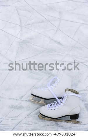 I love ice skating. Ice skates on rink background.