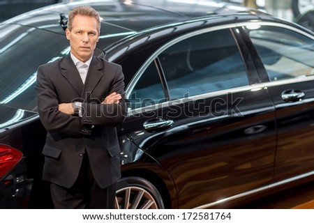 I love luxury cars. Top view of confident grey hair man in formalwear leaning at the car and looking at camera - stock photo