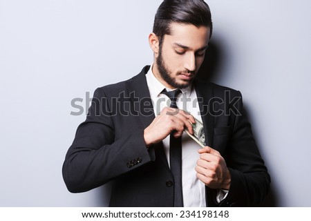 I love money and they love me. Handsome young man in formalwear putting money in his pocket while standing against grey background - stock photo