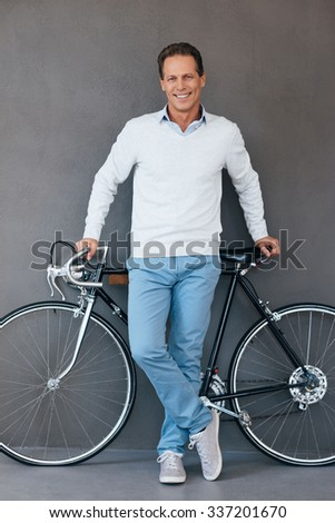 I love my bike! Confident mature man leaning at his bicycle and smiling while standing against grey background  - stock photo