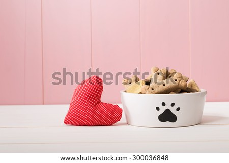 I Love My Dog concept with a red textile heart alongside a doggy bowl decorated with a paw print and filled with biscuits, pink background with copyspace - stock photo