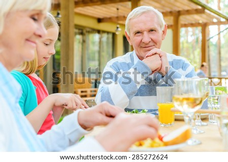 I love my family! Happy senior man looking camera and smiling while enjoying dinner together with her family  - stock photo