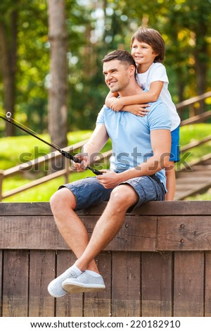 I love my father! Happy father and son fishing together on quayside - stock photo