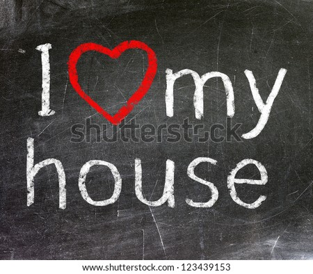 I love my house handwritten with white chalk on a blackboard.
