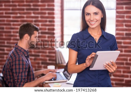I love my job! Beautiful young woman holding digital tablet and smiling while man sitting in the background and working on laptop  - stock photo