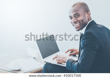 I love my job! Cheerful young African businessman typing something on laptop and looking over shoulder - stock photo