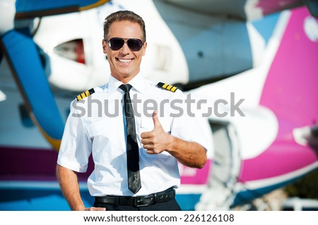 I love my job! Confident male pilot in uniform showing his thumb up and smiling while standing in front of the airplane - stock photo