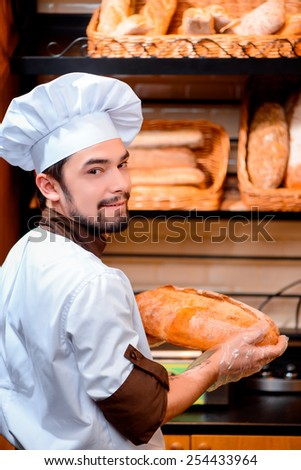 I love my job. Handsome young baker in apron looking over his shoulder and smiling while standing with a loaf of bread against rows of fresh baked bread in the bakery shop - stock photo