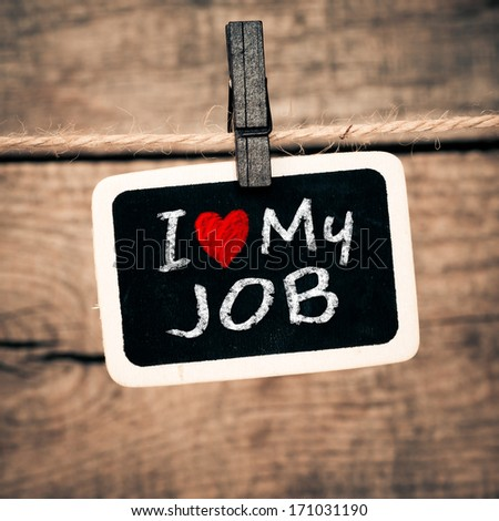 I love my job handwritten with white chalk on old photo and clothes peg on a wooden background - stock photo